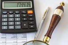 Una calculadora, Pen And Magnifying Glass Sit en una página con números imagenes de archivo