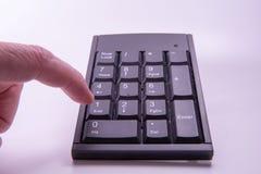 Una calculadora y un finger Fotos de archivo