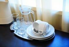 Una caldera eléctrica y una bandeja con una jarra, vidrios, tazas, platillos, cucharas en una tabla en una habitación Fotos de archivo