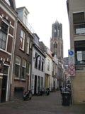 Una calle cobbled bici-alineada magnífica que lleva al Domtoren en Utrecht, los Países Bajos foto de archivo