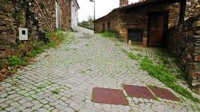 Una calle cobbled con las casas rústicas en pueblo del esquisto de Pena metrajes