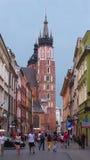 Una calle con una torre de la iglesia del St Mary en Kraków, Polonia imagenes de archivo