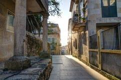 Una calle en Pontevedra España con el sol que brilla Columnas de piedra y un balcón con las plantas horizontal Foto de archivo