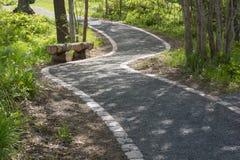 Una calzada en un parque con un banco de madera en el lado foto de archivo