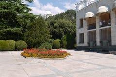 Una cama de flor en un fondo de un edificio, de arbustos decorativos redondos y de abetos Fotografía de archivo libre de regalías