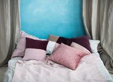Una cama matrimonial con las almohadas se coloca cerca de una pared de azul cielo, foto de archivo