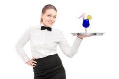 Una camarera con la pajarita que sostiene una bandeja con el cóctel en él bandeja Imagen de archivo libre de regalías