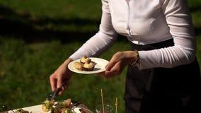 Una camarera en uniforme arregla los aperitivos en las placas metrajes