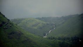 Una Camera al seminterrato delle cadute dell'acqua in mezzo delle colline e greenary fotografia stock