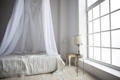 Una camera da letto accogliente nei colori pastelli con un grande letto, una lampada da tavolo o Immagini Stock Libere da Diritti