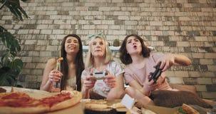 In una camera da letto moderna con signore degli amici le belle di una progettazione tre che giocano in PlayStation e che mangian archivi video