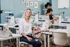 Una camicia bianca d'uso della donna bionda graziosa Smart di aspetto sta cucendo con la cucire-macchina elettrica Modo, sarto immagini stock