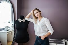 Una camicia bianca d'uso della donna bionda graziosa Smart di aspetto sta stando accanto al manichino di un sarto Modo, l'officin fotografie stock