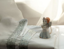 Una camisa bautismal del algodón para un bebé recién nacido y un ángel de la porcelana puestos en él Imagen de archivo libre de regalías
