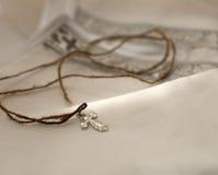 Una camisa bautismal del algodón para un bebé recién nacido y una cruz en una secuencia gruesa colocada en ella Imagen de archivo libre de regalías