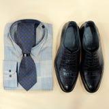 Una camisa con un lazo y los zapatos mienten en un piso beige Complementos del hombre moderno Marco cuadrado para hacer publicida foto de archivo libre de regalías
