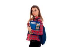 Una camisa del ` s de la chica joven en la caja se coloca oblicua y que sostiene una carpeta con los cuadernos Imagen de archivo