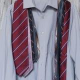 Una camisa del ` s de los hombres con cinco lazos que cuelgan en una suspensión en un backgrou Fotografía de archivo libre de regalías