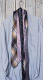 Una camisa del ` s de los hombres con cinco lazos que cuelgan en una suspensión en un backgrou Foto de archivo libre de regalías