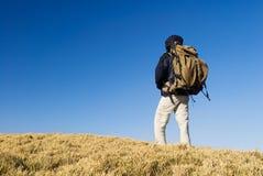 Una camminata del viaggiatore con zaino e sacco a pelo su un pascolo giallo in mountai Fotografie Stock