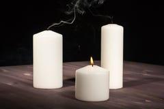 Una candela bruciante e due estinti Immagine Stock