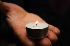 Una candela d'ardore bruciante nella sua equipaggia la mano Immagine Stock