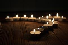 Una candela e candele su vecchio fondo di legno Immagine Stock Libera da Diritti