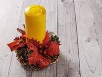 Una candela gialla e un pino del nuovo anno si avvolgono su un vecchio fondo di legno Fotografie Stock Libere da Diritti