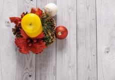 Una candela gialla e un pino del nuovo anno si avvolgono su un vecchio fondo di legno Immagine Stock