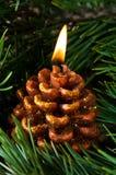 Una candela gradice il cono del pino Immagine Stock