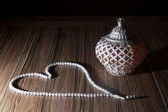 Una candela leggera dorata di Ramadhan con il rosario bianco islamico borda la o immagine stock