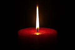 Una candela su una priorità bassa nera immagini stock