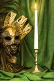 Una candela in un candeliere vicino ad una maschera veneziana su un backgr verde Fotografia Stock