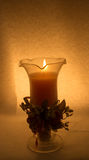 Una candela in un vetro su un fondo bianco fotografia stock libera da diritti