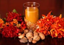 Una candela in una regolazione di autunno Fotografia Stock