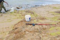 Una canna da pesca, un secchio e un pescatore su una spiaggia al minimo Immagini Stock Libere da Diritti