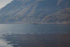 Una canoa di quattro uomini nel lago fotografie stock