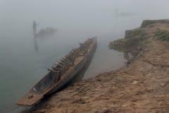 Una canoa nepalesa de madera nacional con las cisternas invertidas hace una pausa la orilla, otros barcos navega a lo largo del r Fotografía de archivo libre de regalías