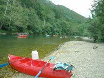 Una canoa roja descansa sobre una orilla rocosa de un lago azul tranquilo en las aguas del límite del río Asturias de Sella imágenes de archivo libres de regalías