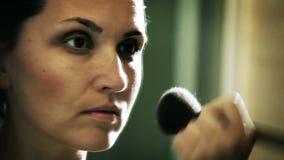 Una cantidad entonada muy elegante de una mujer que aplica su maquillaje antes de una tarde grande almacen de video
