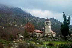 Una capilla en un pequeño cementerio del pueblo detrás de una cerca en el fondo de montañas en tiempo nublado Se empa?a el primer fotografía de archivo