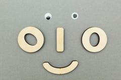 Una cara de madera divertida en un fondo gris imagen de archivo libre de regalías
