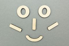 Una cara de madera divertida en un fondo gris imagen de archivo