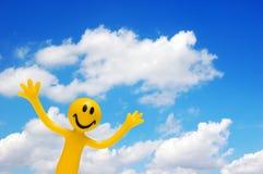Una cara feliz y un cielo azul foto de archivo