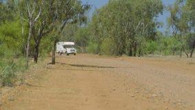 Una caravana que invierte abajo de una pista de tierra almacen de metraje de vídeo