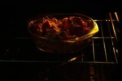 Una carne asada más caliente en el horno, el guisado vegetal se cuece en una forma de cristal en el horno foto de archivo