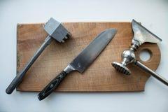 Una carne del martillo y un cuchillo y un hacha de la cocina en una cubierta de madera imagenes de archivo