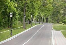 Una carretera de asfalto de la bobina y una acera para los peatones a través del parque con varias lámparas hermosas del vintage Imagen de archivo
