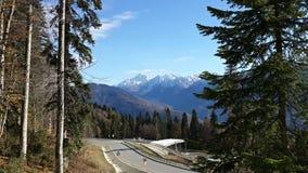 Una carretera de la montaña y picos coronados de nieve Foto de archivo