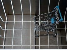 Una carretilla de las compras, una cesta y un congelador vacíos de la caja foto de archivo libre de regalías
